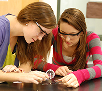 Girls inspecting broken glass with a magnifying glass