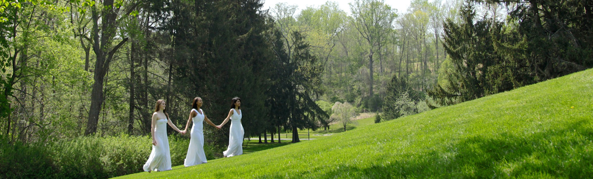 Oldfields Girls walking up graduation hill in white dresses